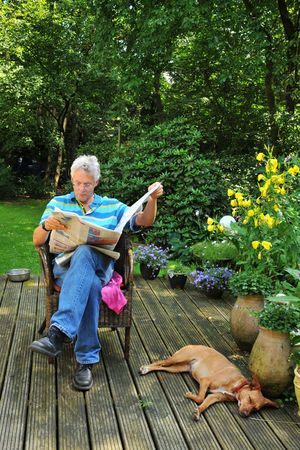 Senior man is reading newspaper outdoor photo