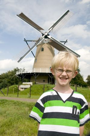 Little boy is in Holland in front of a Dutch windmill Stock Photo - 3455430