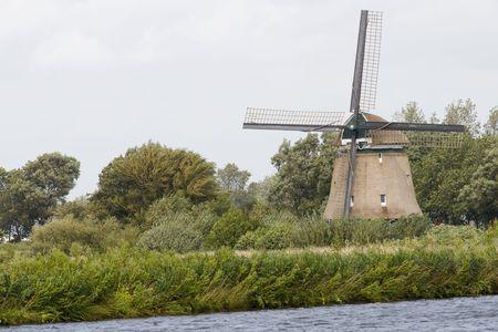 Windmill in Dutch landscape near the river photo