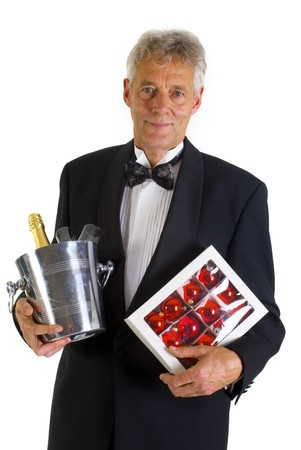 Elderly man in tuxedo with champagne and christmas balls photo