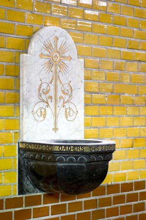 catholism: Holy water font in church with Dutch text In the name of the father