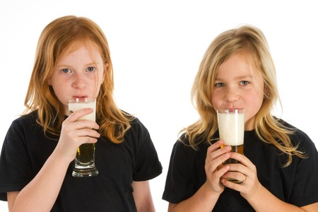 Two little children drinking a glass of beer photo