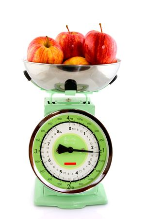 The weight of red apples at a retro kitchen scale photo