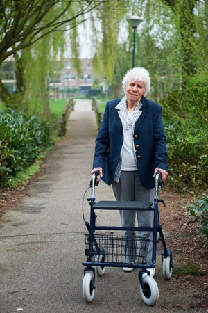 Very old lady with blue walker walking outdoor photo