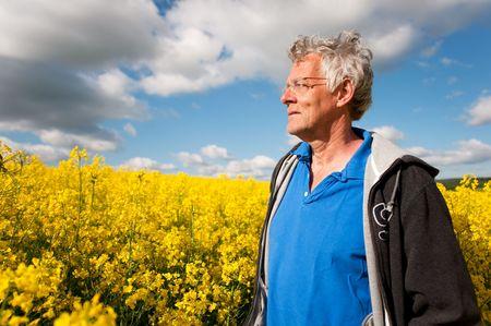 coleseed: elderly man standing in coleseed fields