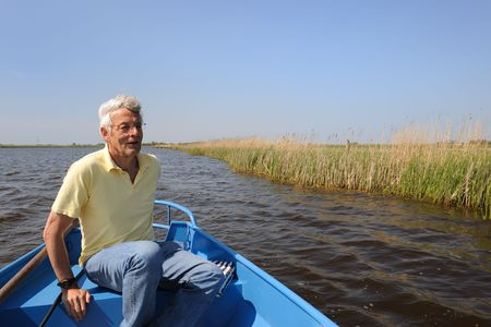 polder: Senoir man is with boat in polder nature Stock Photo