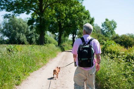 Elderly man is walking with his dog in nature photo