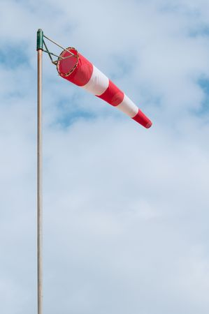 Red and white windsock on a pole photo