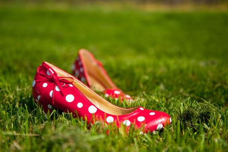 speckles: Red speckles ladies shoes in green gras Stock Photo