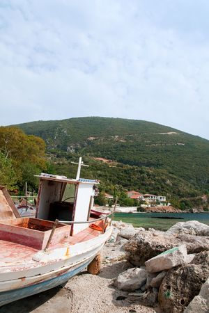 fisherman on boat: Greek landscape with old fisherman boat near the coast at Lefkas