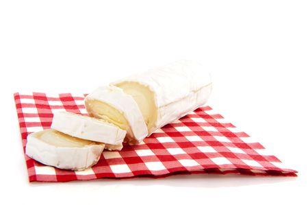 queso de cabra: Queso de cabra fresco sobre una servilleta de cuadros rojos Foto de archivo