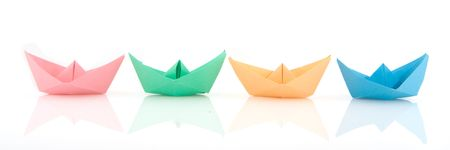 Paper boats in different colors in a row photo