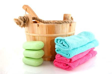 wooden sauna bucket with spoon towels and soap photo