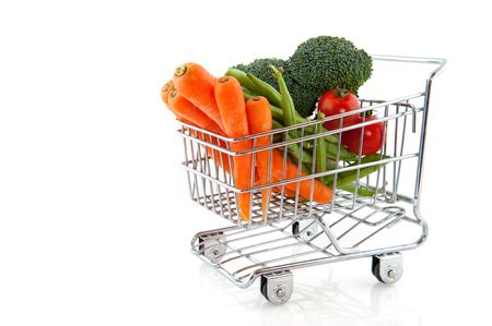 shopping cart with fresh vegetables isolated over white photo