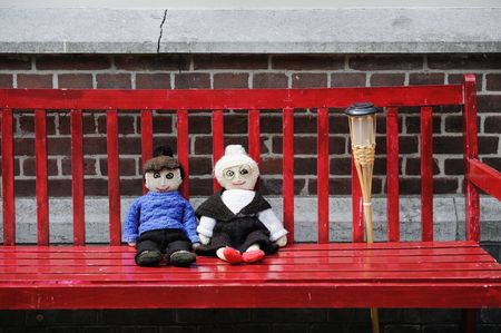handmade elderly knitted couple outdoor at the red bench photo