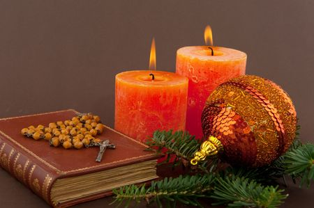 dross: christmas candle and bible with rosary on brown