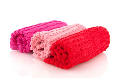 Rolled towels in pink and red isolated over white photo