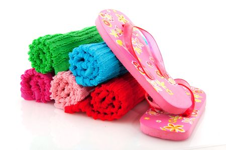 colorful rolled towels from terry with flip flops for vacation photo