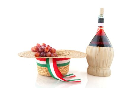 Basket bottle with Chianti grapes and hat from Italy over white photo