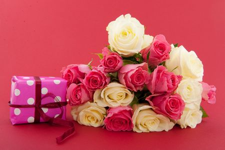 mixed flower bouquet: bouquet birthday roses in pink and white on red background with present