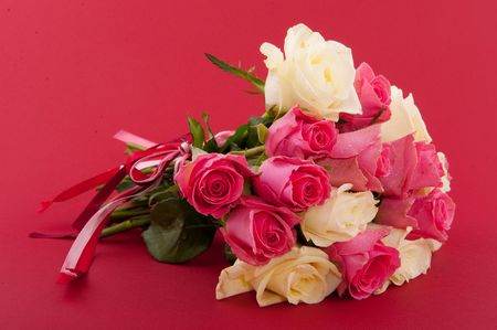 mixed flower bouquet: bouquet roses in pink and white on red background