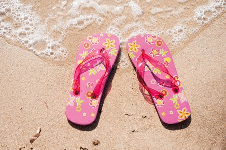 summer vacation at the beach with flip flops in the water photo