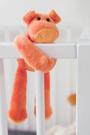 stuffed orange colorful animal on baby bed  photo