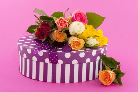Bouquet many colorful roses and a birthday present on pink photo