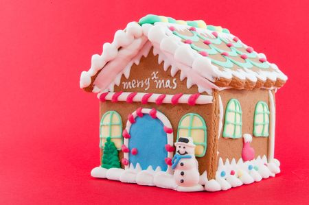 Ginger bread house isolated on red background photo