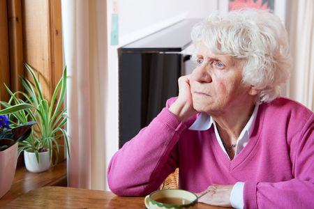 Elderly lonely woman depressed sitting at the table Stock Photo - 5980294