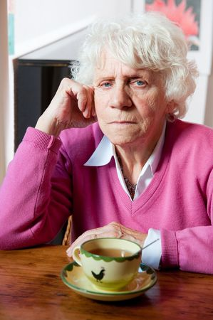 Elderly lonely woman depressed sitting at the table  Stock Photo