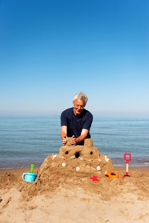 making hole: Elderly man is building a sand castle at the beach with plastic toys