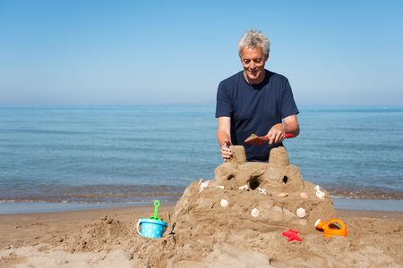 Elderly man is building a sand castle at the beach with plastic toys photo
