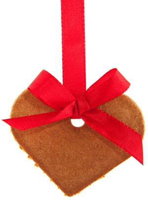 Gingerbread heart with red ribbon hanging as a garland photo