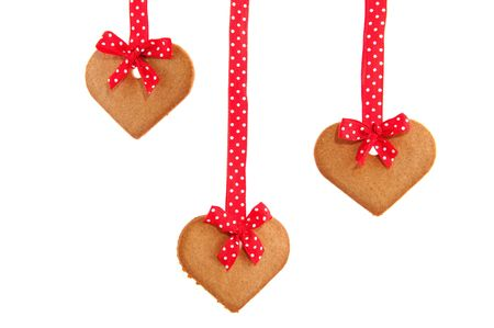 speckles: Baked hanging gingerbread hearts with red speckles bows and ribbon Stock Photo