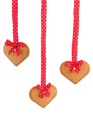Baked gingerbread hearts with red speckles bows and ribbon photo