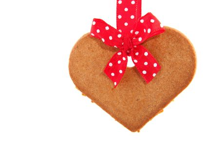 Baked gingerbread heart coookie with red speckles bows and ribbon photo