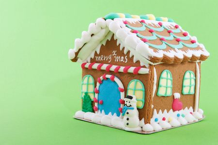 Cheerful gingerbread house on a green background photo