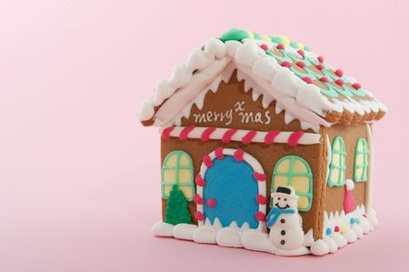 Cheerful gingerbread house on a pink background photo