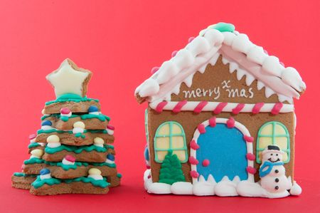 Cheerful gingerbread house and tree on a red background photo