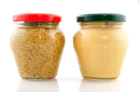 two different kinds of mustard in glass pot photo