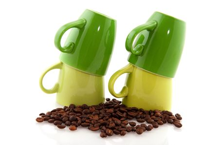 Green coffee mugs with beans isolated over white photo