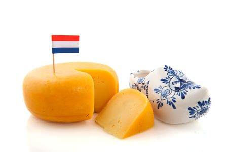 Dutch cheese with flag and clogs isolated over white photo