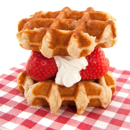 Waffles with strawberries and whipped cream on napkin photo
