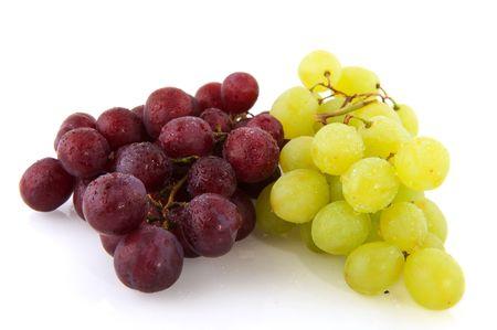 uvas: Uvas frescas de rojas y blancas con gotas de agua aislados sobre blanco  Foto de archivo