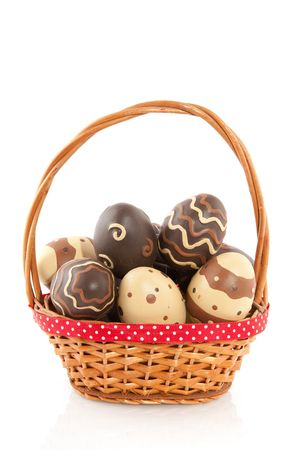 Basket filled with chocolate easter eggs isolated over white photo