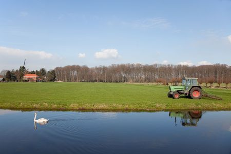 Mowing the grass in the fields with tractor photo