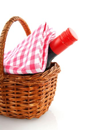 picnic basket with a bottle of wine and checkered cloth photo