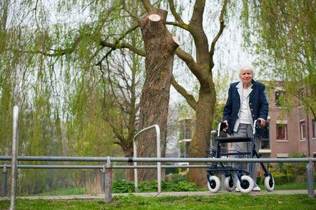 elderly woman with walker walking in the park photo
