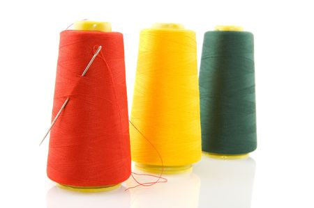 three bobbin with colorful threads in a row photo